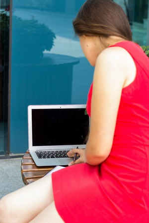 lap top: Young woman using lap top onthe street Stock Photo
