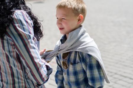 niños vistiendose: joven madre vestir a su pequeño hijo