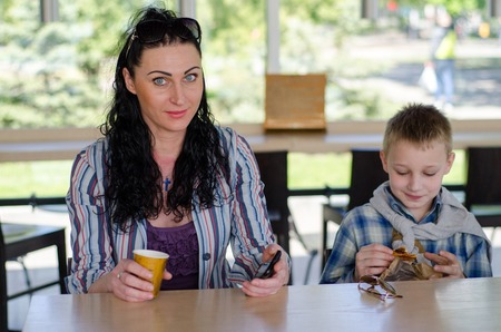 cofee: girl drinking cofee in the cafe with her son Stock Photo