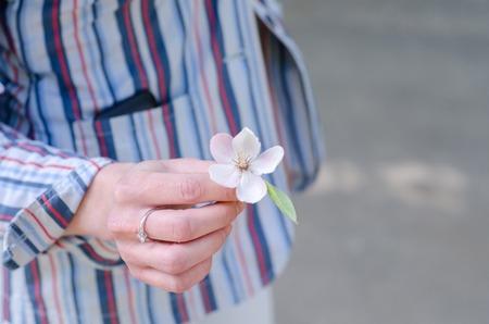 girl holding flower: close up of girl holding flower in her hand