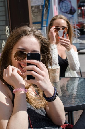 two person only: Two girlfriends are using cellphones in the cafe