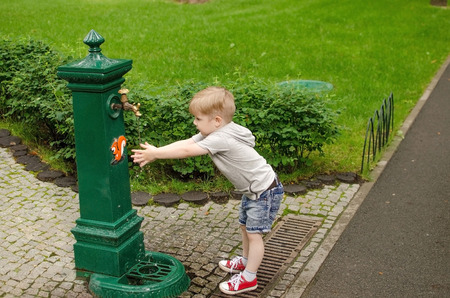 Small baby boy is washing hands in the park