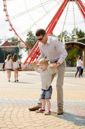 Small baby boy is having fun with his father in the park Stock Photo