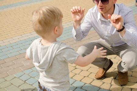 Small baby boy is having fun in the park with his father Stock Photo