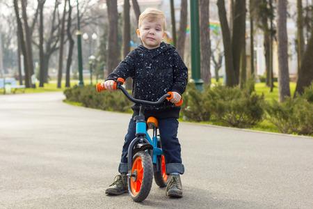 blinking: Little boy on the run bike is blinking