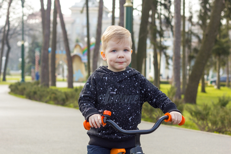 dimple: Little boy with a dimple on his cheek is riding a run bike