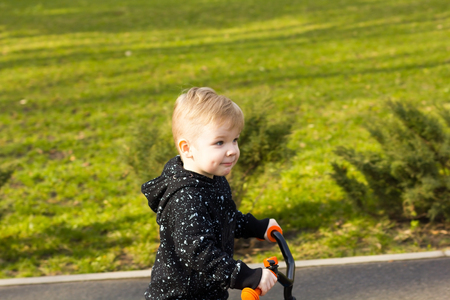 cheek to cheek: Little boy with a dimple on his cheek on the run bike