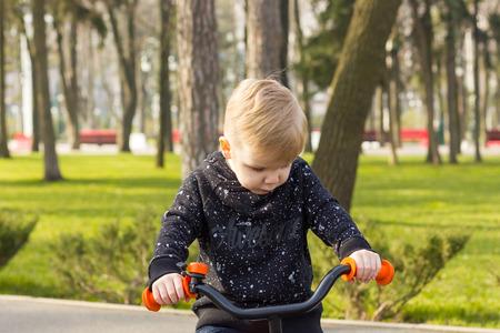 hoody: Little boy in black hoody on the run bike is looking down Stock Photo