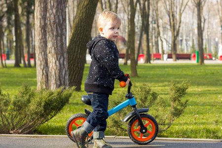 looking aside: Little boy standing near the run bike and looking aside Stock Photo