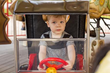 handling: Little boy is handling steering wheel Stock Photo