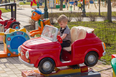 cabriolet: Small boy sitting in red toy cabriolet in the park Stock Photo