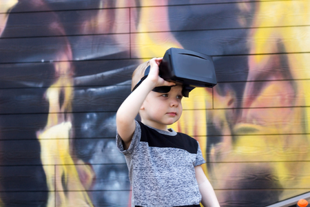 looking aside: Boy in t-shirt with the virtual glasses looking aside