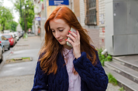 Young red woman using her cell phone