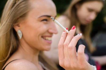 Young woman is smoking on the street Stock Photo