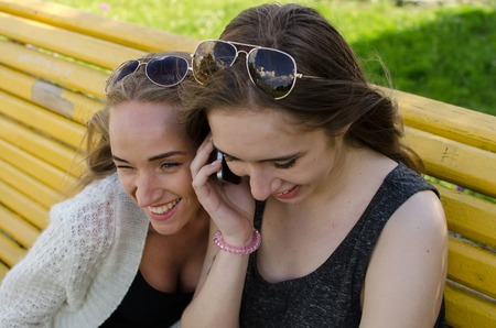 Two girlfiends with the telephones on the street Stock Photo