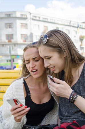 two persons only: Two girlfiends with the telephones on the street Stock Photo