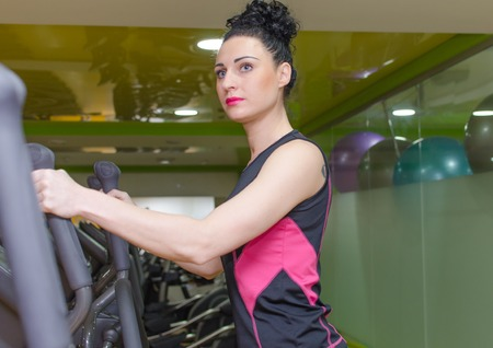 Young woman is training on elliptical trainer
