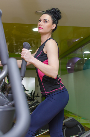 elliptical: Young woman is training on elliptical trainer