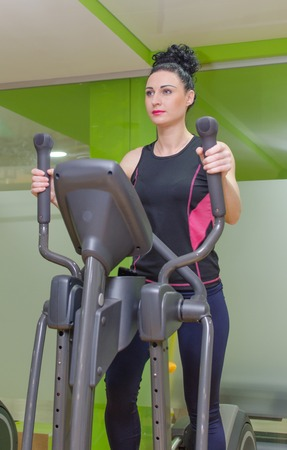 eliptica: Young woman is training on elliptical trainer