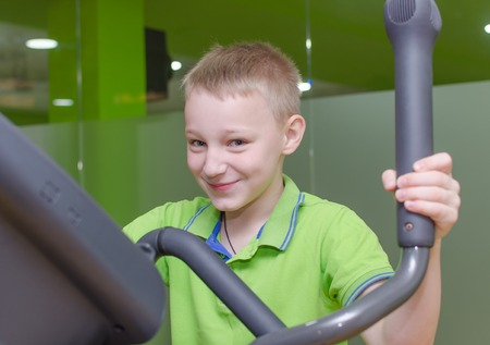 eliptica: Mother and son are training on the elliptical trainer Foto de archivo