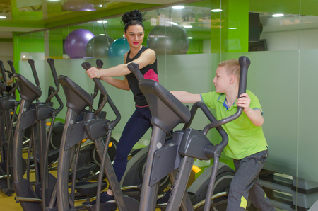 elliptical: Mother and son are training on the elliptical trainer Stock Photo