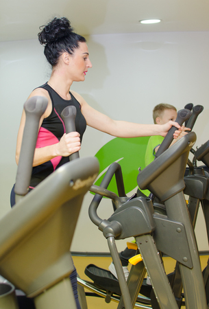 Mother and son are training on the elliptical trainer Stock Photo