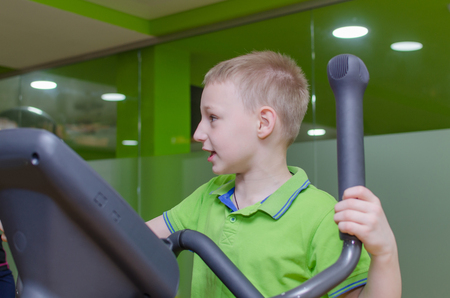 elliptical: Young boy is training on the elliptical trainer
