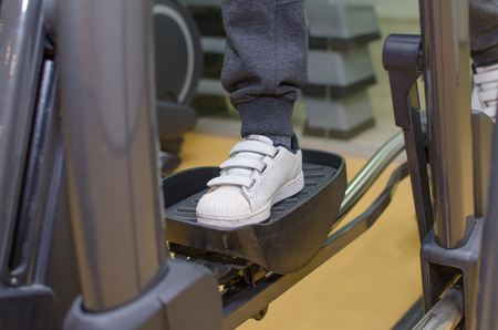 eliptica: Young boy is training on the elliptical trainer