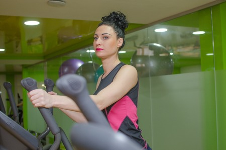 elliptical: Young woman is training on the elliptical trainer