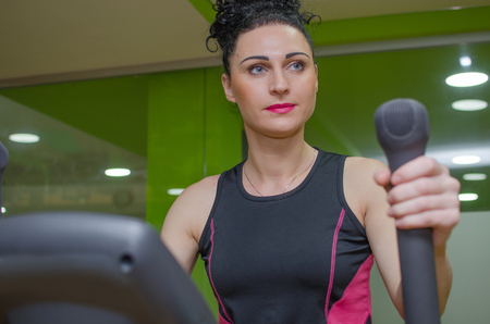 eliptica: Young woman is training on the elliptical trainer