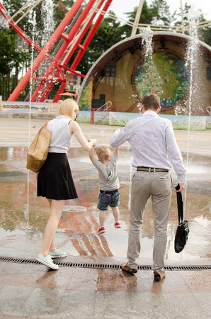 interesting: Young family is walking in the park during the summer