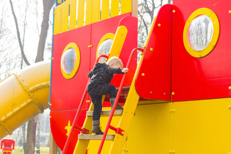 almost: Small boy is almost on the top of the ladder Stock Photo
