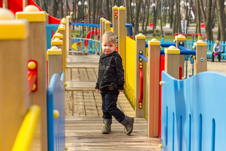 dimple: Small boy with dimple bending one leg on the wooden bridge