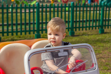 Small boy in the grey t-shirt is sitting in cabriolet and frowning