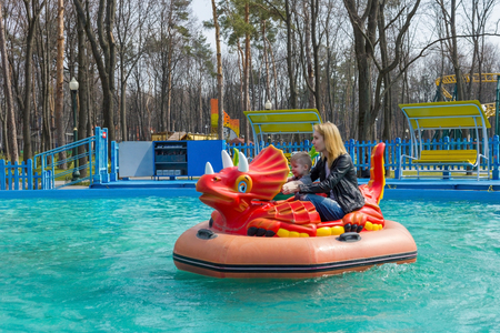 dragon swim: Mother and son riding red dragon attraction