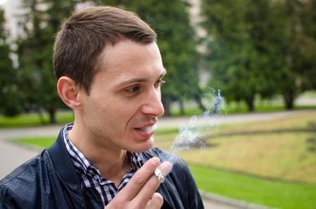 joven fumando: Young man smoking cigarette on the street