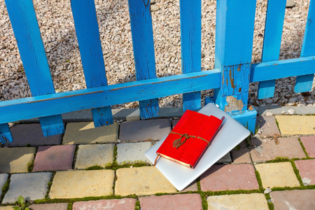 Notebook with notebook on it beside the fence Stock Photo