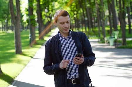 Young man using his phone on the street Stock Photo