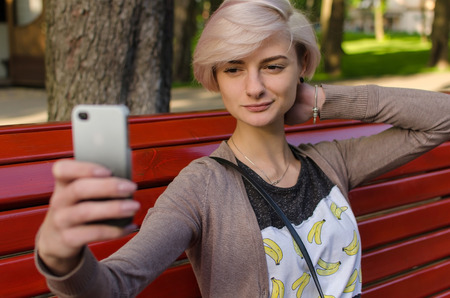 Young girl sitting on the bench in the park and making selfie