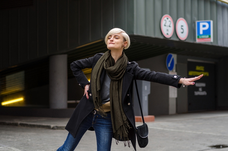 catching taxi: Young blonde woman catching the taxi on the city street Stock Photo