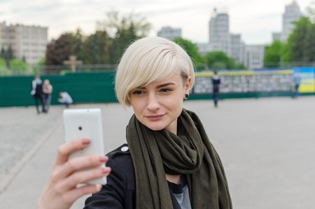 Young blonde girl making selfie in the city