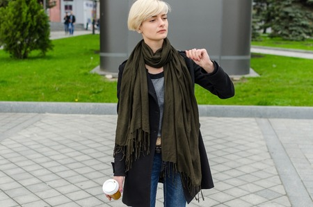 only 1 woman: Young girl with a plastic cup of coffee walking on the cit streets