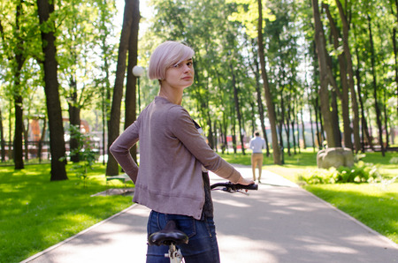 Young beautiful girl riding a white bicycle in the park