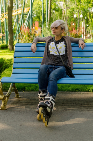 Young girl sitting on the bench wearing black rollers in the park