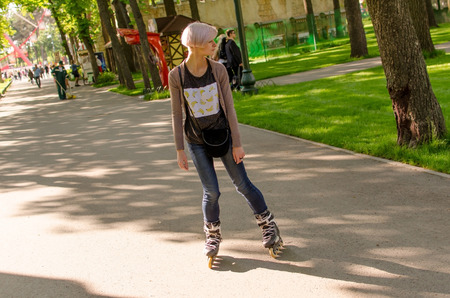 Young beautiful girl rollerblading in the park