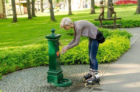 skate park: Young girl with black rollers in the park washing her hands Stock Photo