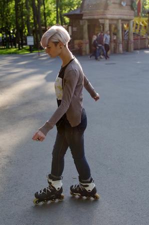 Chica joven y bella en patines en el parque