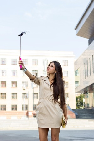 Young woman making seflie with her phone on the street