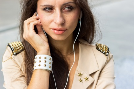 Young woman listenign to music on the street