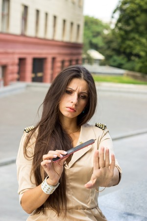 causcasian: Young woman takes care of her nails on the street Stock Photo